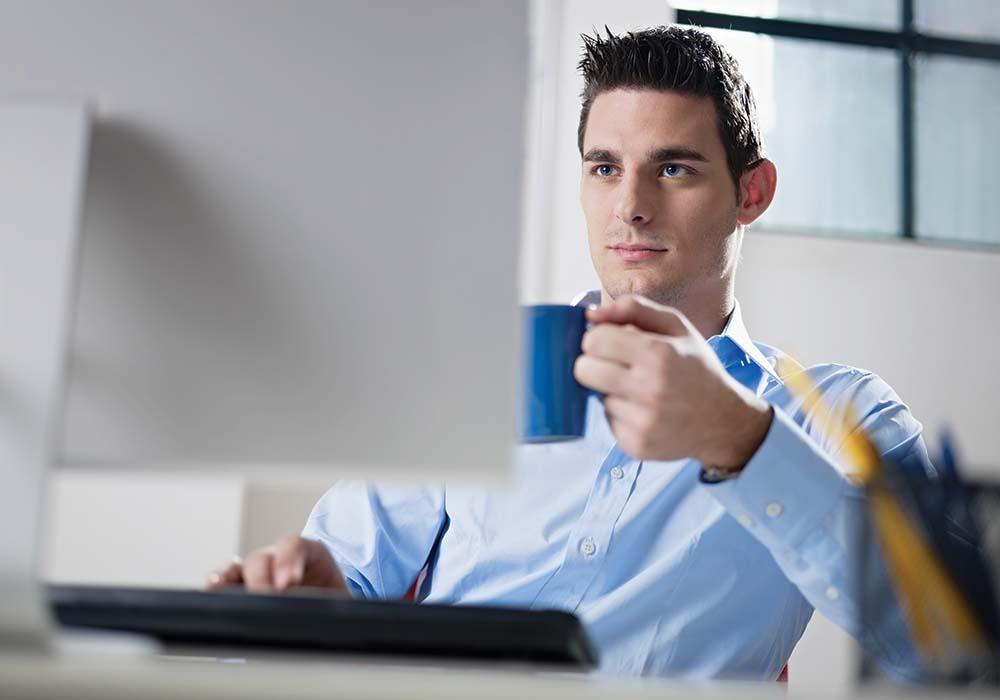 man at computer looking at charge/load management software